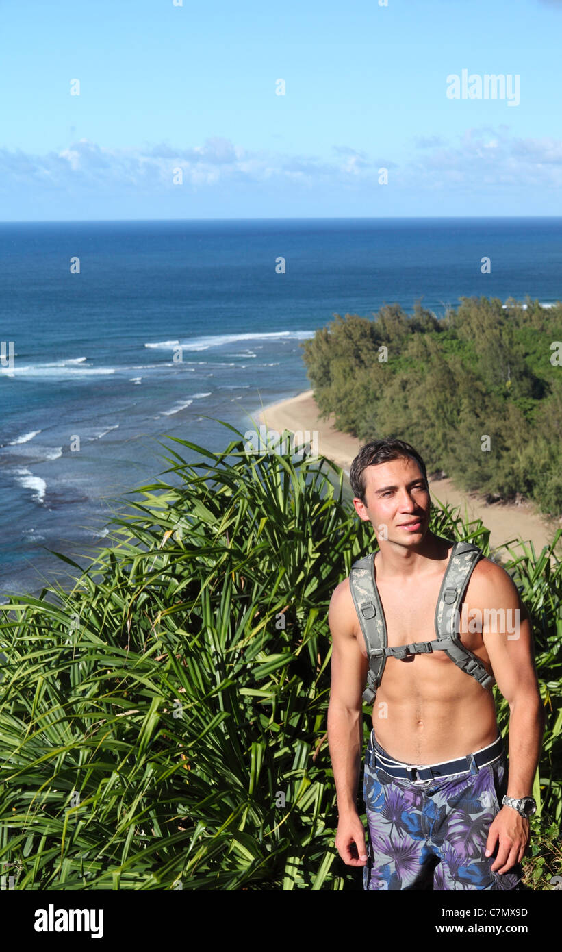 Hiker on the Kalalau Trail on Kauai, with Kee Beach in the background - Stock Image
