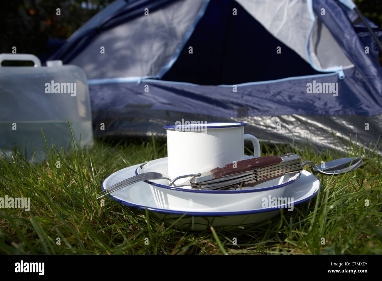 water container tin plate cup and camping tool utensils in front of the open door of a tent - Stock Image