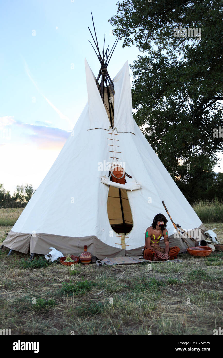 An American Indian boy sits outside a tepee - Stock Image