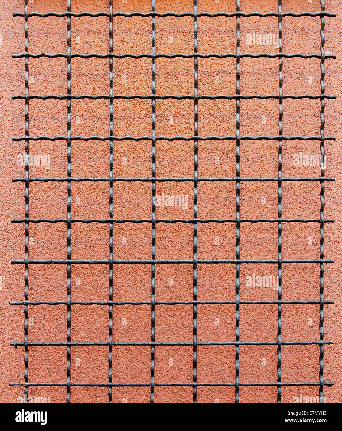 Black wire grid against a salmon stucco wall - Stock Image