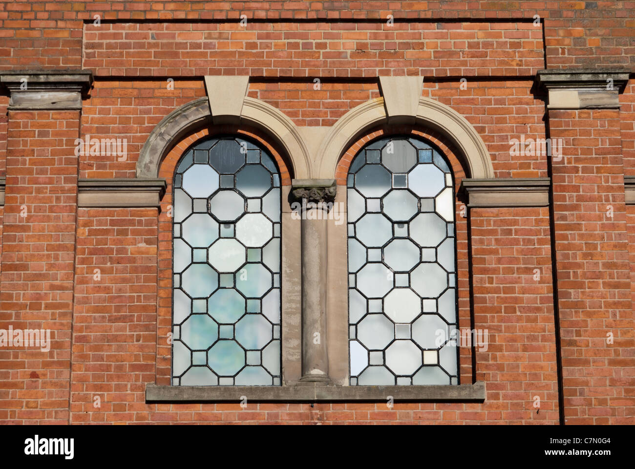 Lead windows in a red brick building - Stock Image