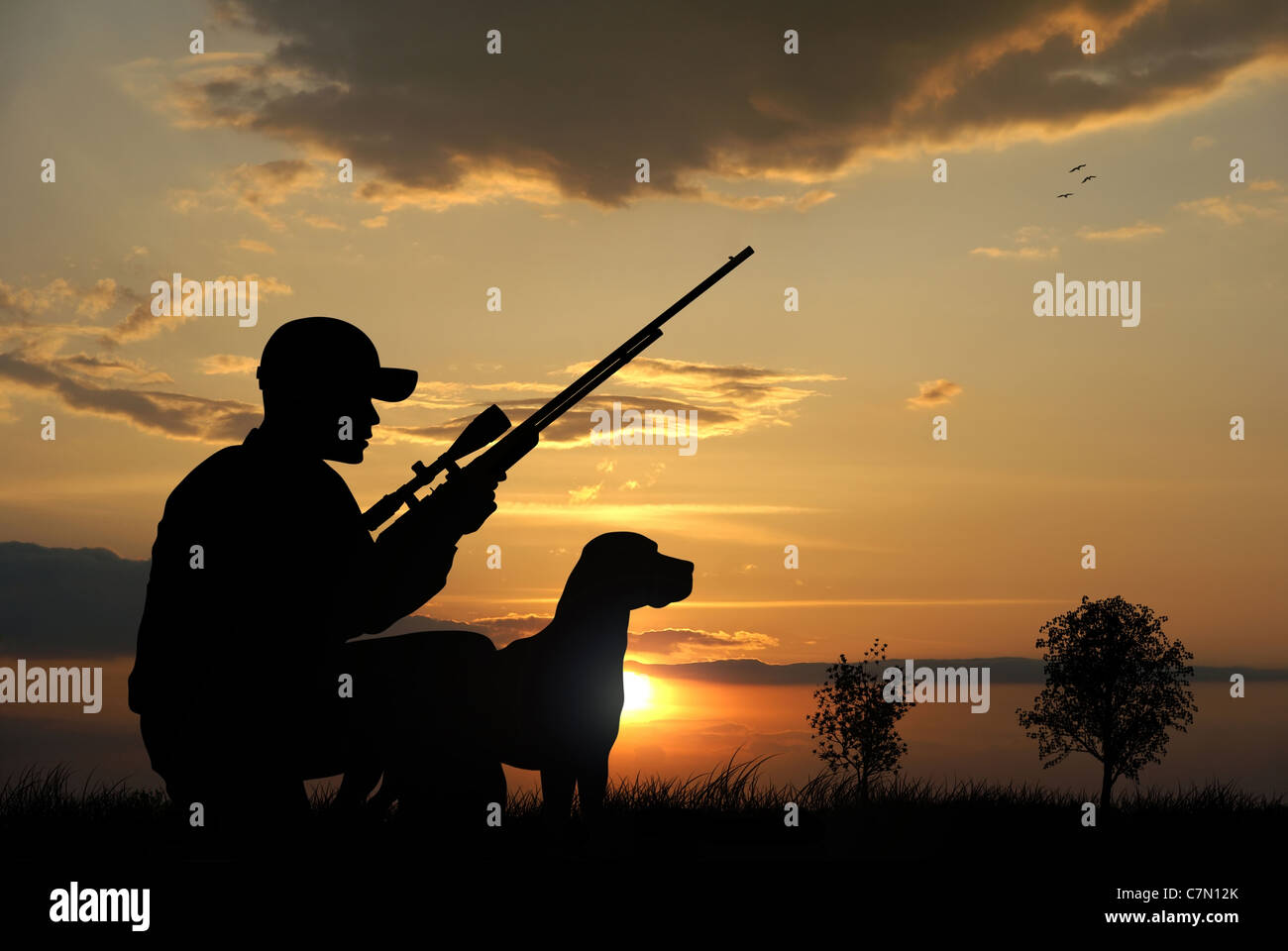 Hunter with his dog silhouettes on sunset background - Stock Image