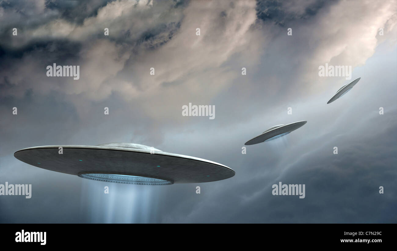 3d render of flying saucers on dramatic clouds background - Stock Image