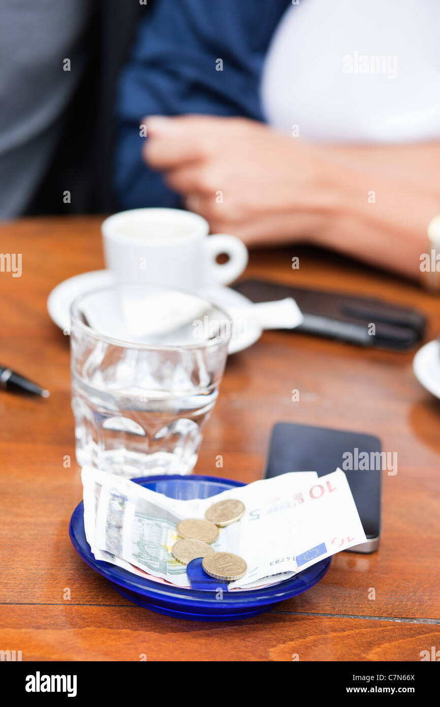 Euro banknotes and coins with bill on a table in a restaurant, Paris, Ile-de-France, France - Stock Image