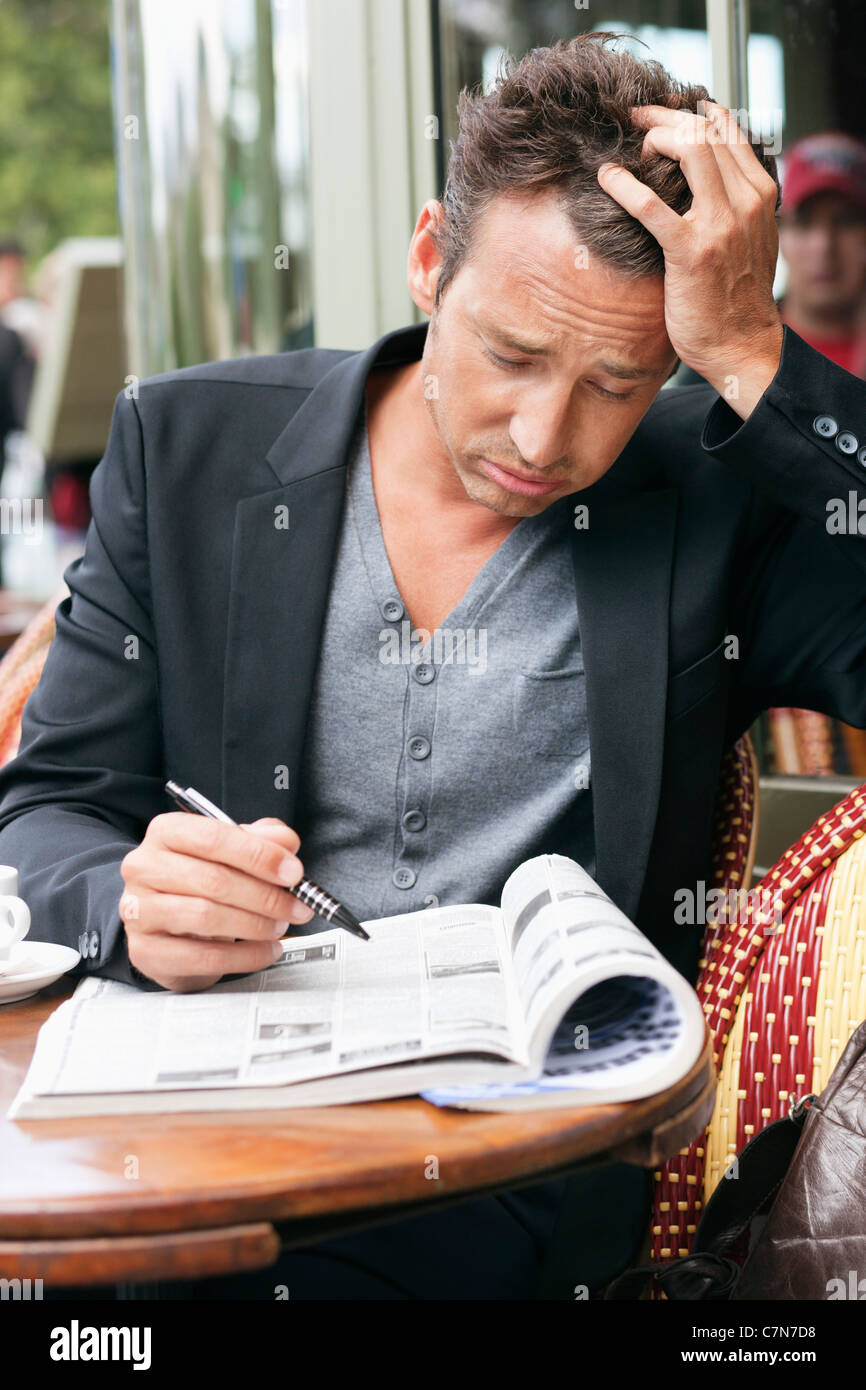 Man reading a magazine looking worried, Paris, Ile-de-France, France - Stock Image