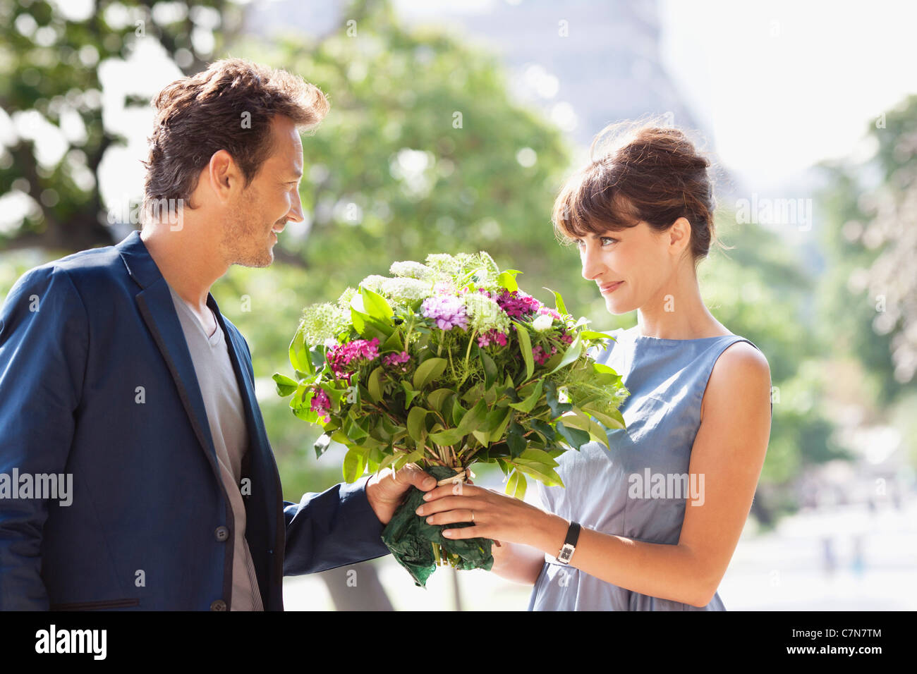 Man giving a bouquet of flowers to a woman with the Eiffel Tower in ...