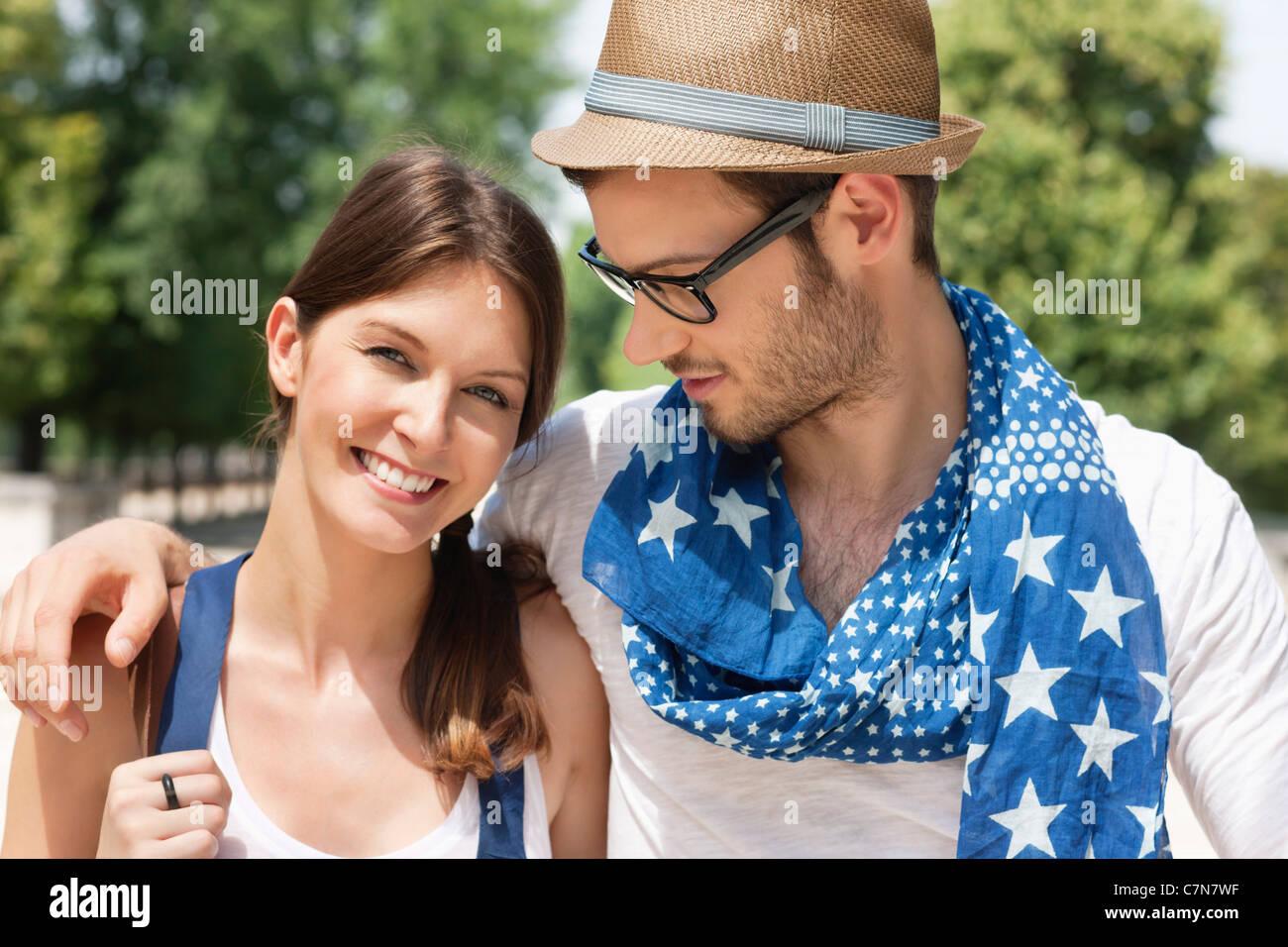Man with his arm around a woman smiling, Paris, Ile-de-France, France - Stock Image
