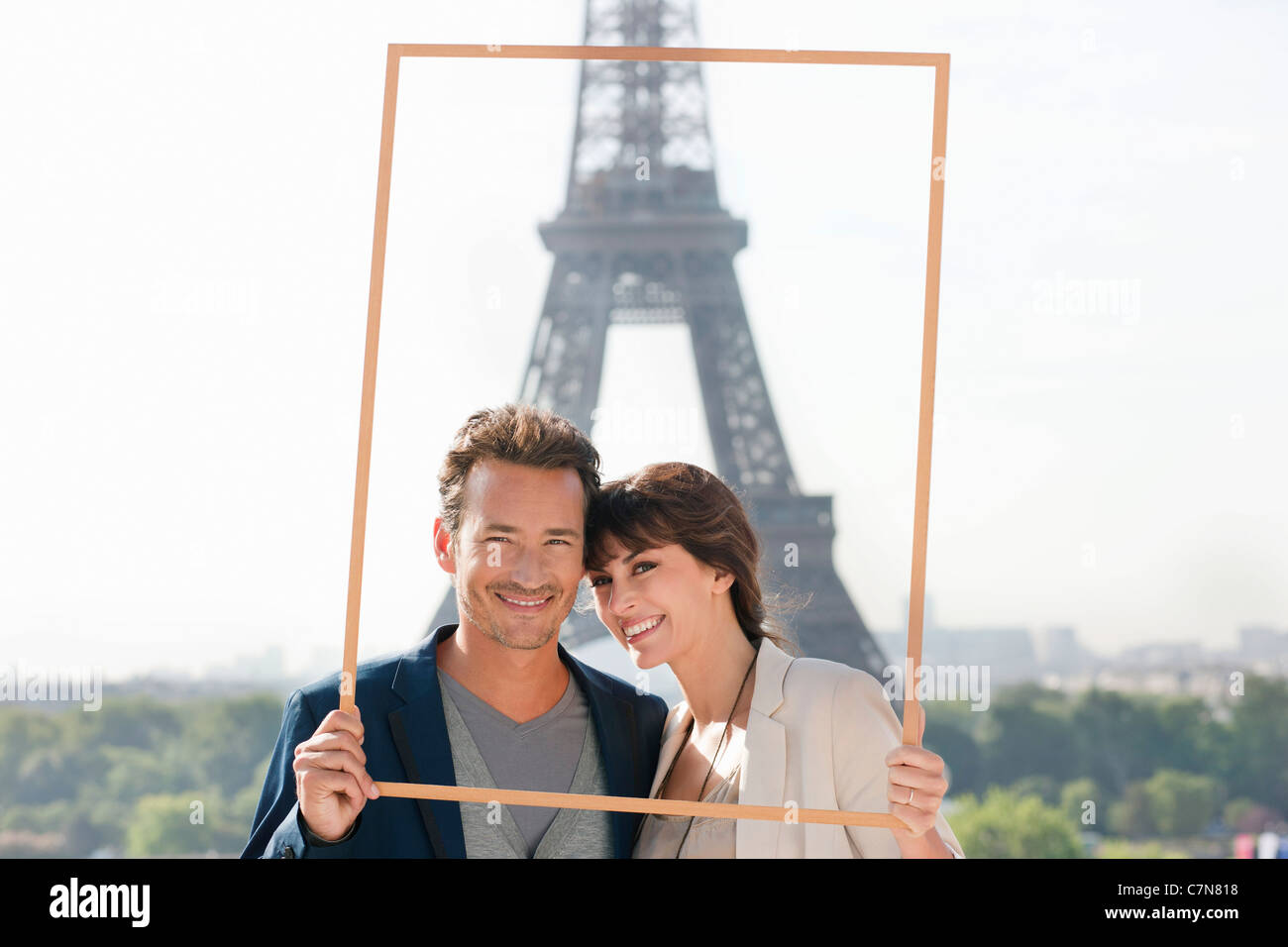 Portrait of a couple framing their dream vacation with Eiffel Tower, Paris, Ile-de-France, France - Stock Image