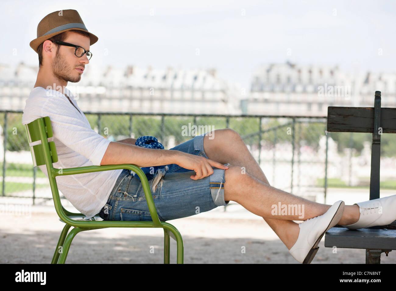 Man resting in a chair, Jardin des Tuileries, Paris, Ile-de-France, France - Stock Image