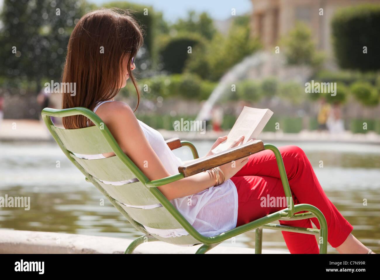 Woman reading a magazine, Jardin des Tuileries, Paris, Ile-de-France, France - Stock Image