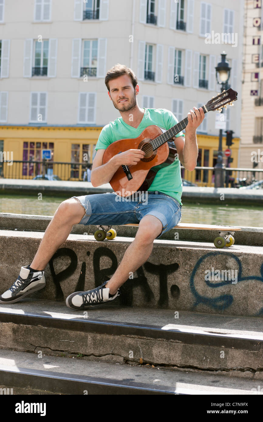 Man playing a guitar, Canal St Martin, Paris, Ile-de-France, France - Stock Image