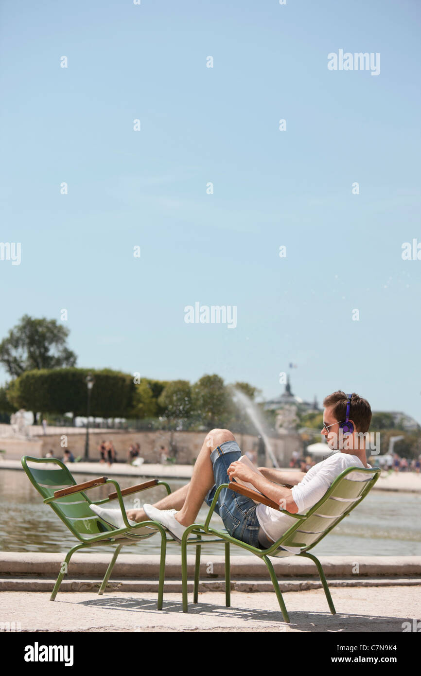 Man sitting in a chair and reading a magazine, Bassin octogonal, Jardin des Tuileries, Paris, Ile-de-France, France - Stock Image