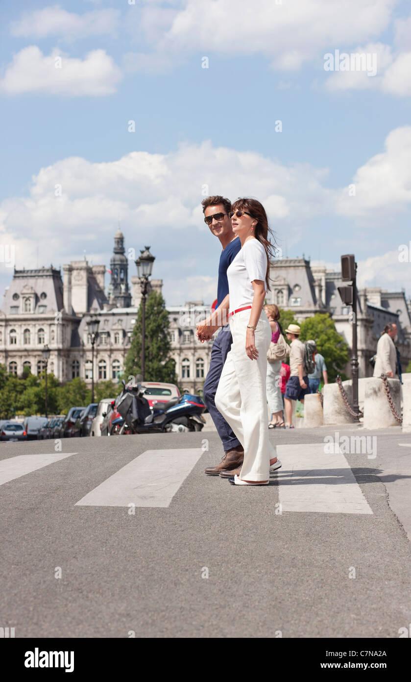 Couple crossing the road, Paris, Ile-de-France, France Stock Photo