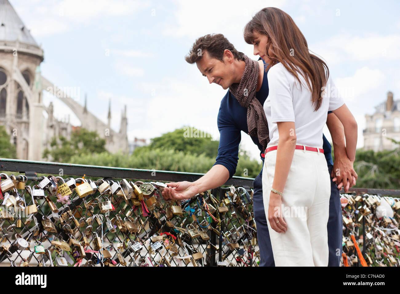 Couple locking a padlock of love on a bridge, Pont des Arts, Notre Dame de Paris, Paris, Ile-de-France, France - Stock Image