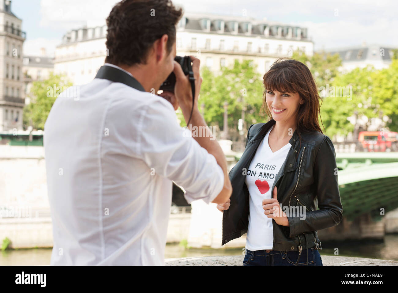 Man taking a picture of a woman with a camera, Seine River, Paris, Ile-de-France, France - Stock Image