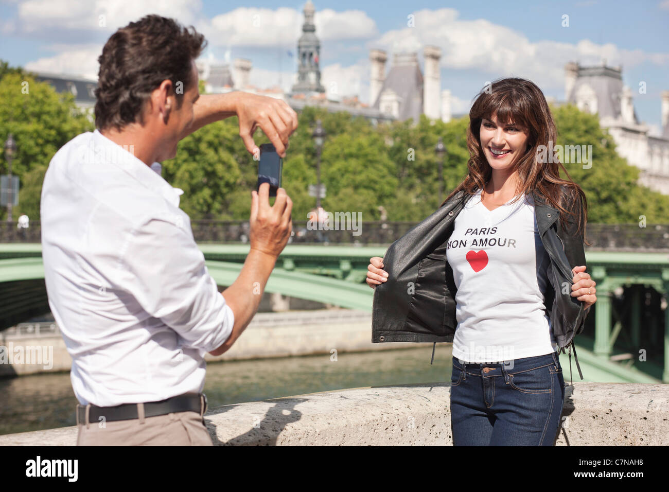 Man taking a picture of a woman with a mobile phone, Seine River, Paris, Ile-de-France, France - Stock Image