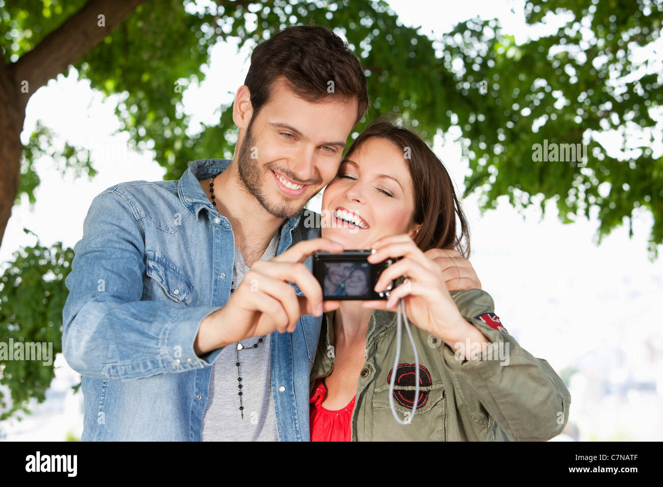 Couple taking a picture of themselves with a digital camera, Paris, Ile-de-France, France - Stock Image