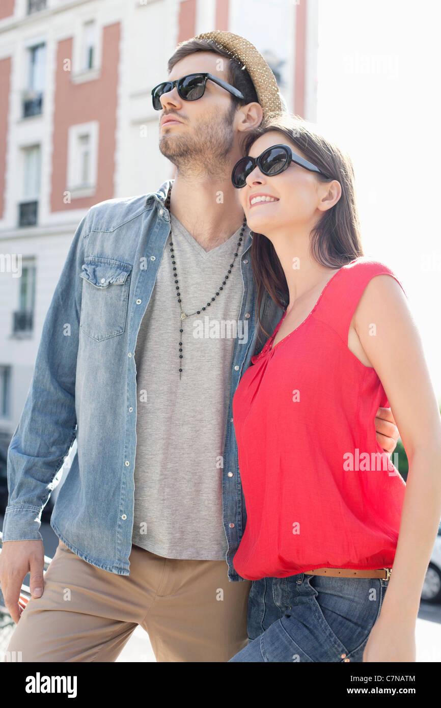 Man standing with his arm around a woman, Paris, Ile-de-France, France - Stock Image