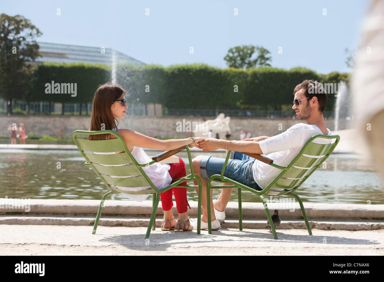 Couple sitting in chairs near a pond, Bassin octogonal, Jardin des Tuileries, Paris, Ile-de-France, France - Stock Image