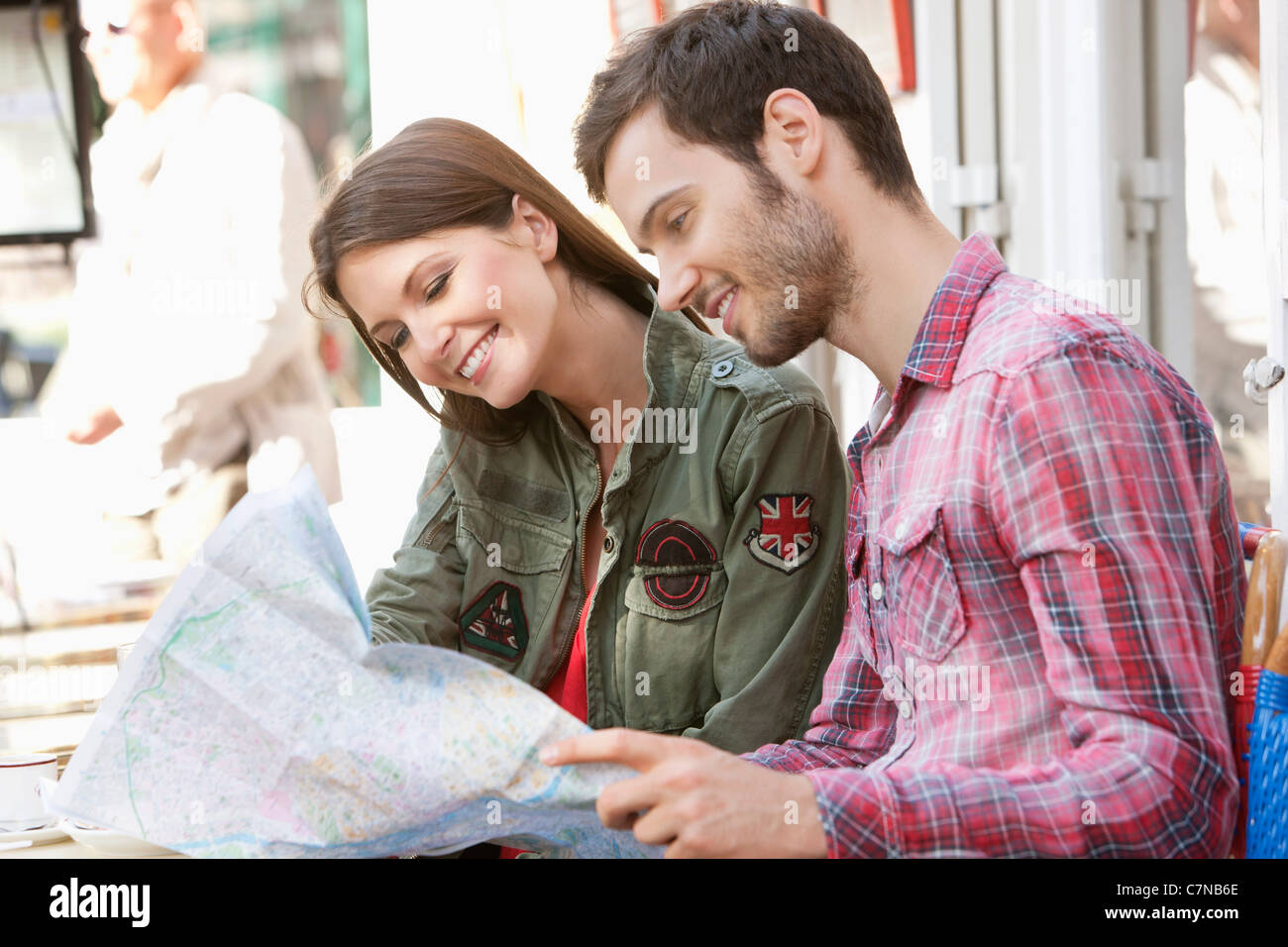 Couple sitting at a sidewalk cafe and reading a map, Paris, Ile-de-France, France - Stock Image