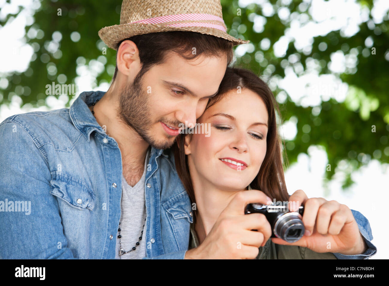 Couple watching photos in a digital camera, Paris, Ile-de-France, France - Stock Image