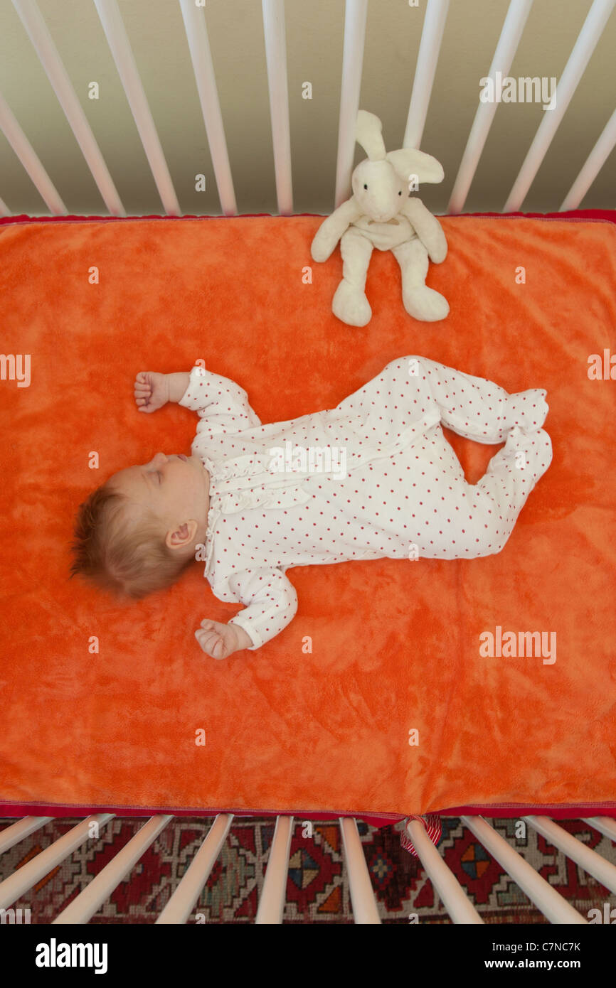 baby sleeping in a crib - Stock Image