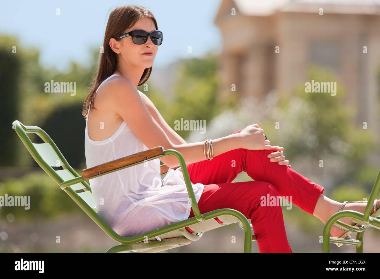 Woman sitting in a chair, Bassin octogonal, Jardin des Tuileries, Paris, Ile-de-France, France - Stock Image