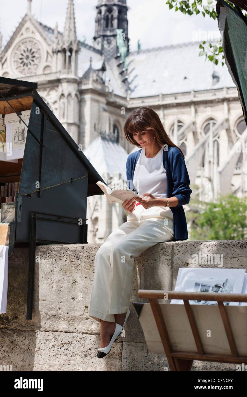 Woman reading a book at a book stall, Notre Dame de Paris, Paris, Ile-de-France, France - Stock Image