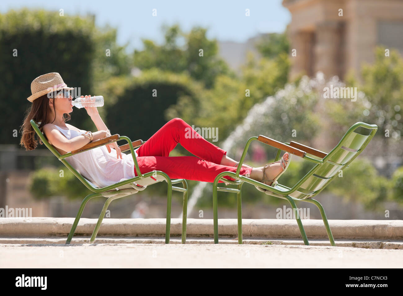 Woman sitting in a chair and drinking water, Bassin octogonal, Jardin des Tuileries, Paris, Ile-de-France, France - Stock Image