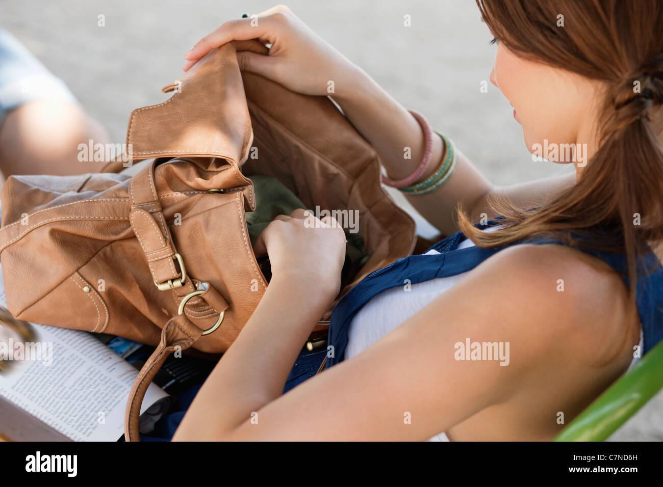 Woman checking her purse, Paris, Ile-de-France, France - Stock Image