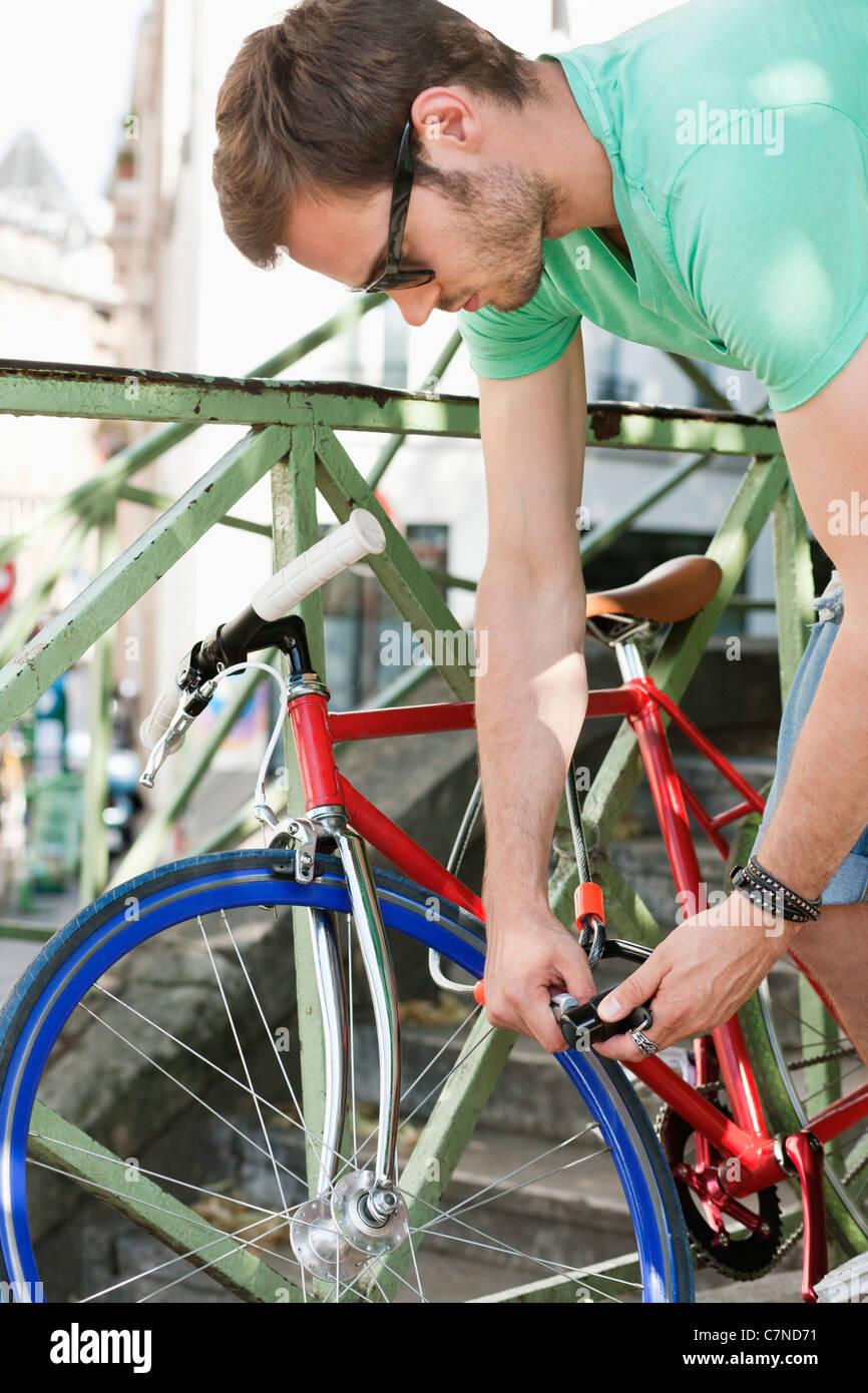 Man locking his bicycle, Paris, Ile-de-France, France - Stock Image