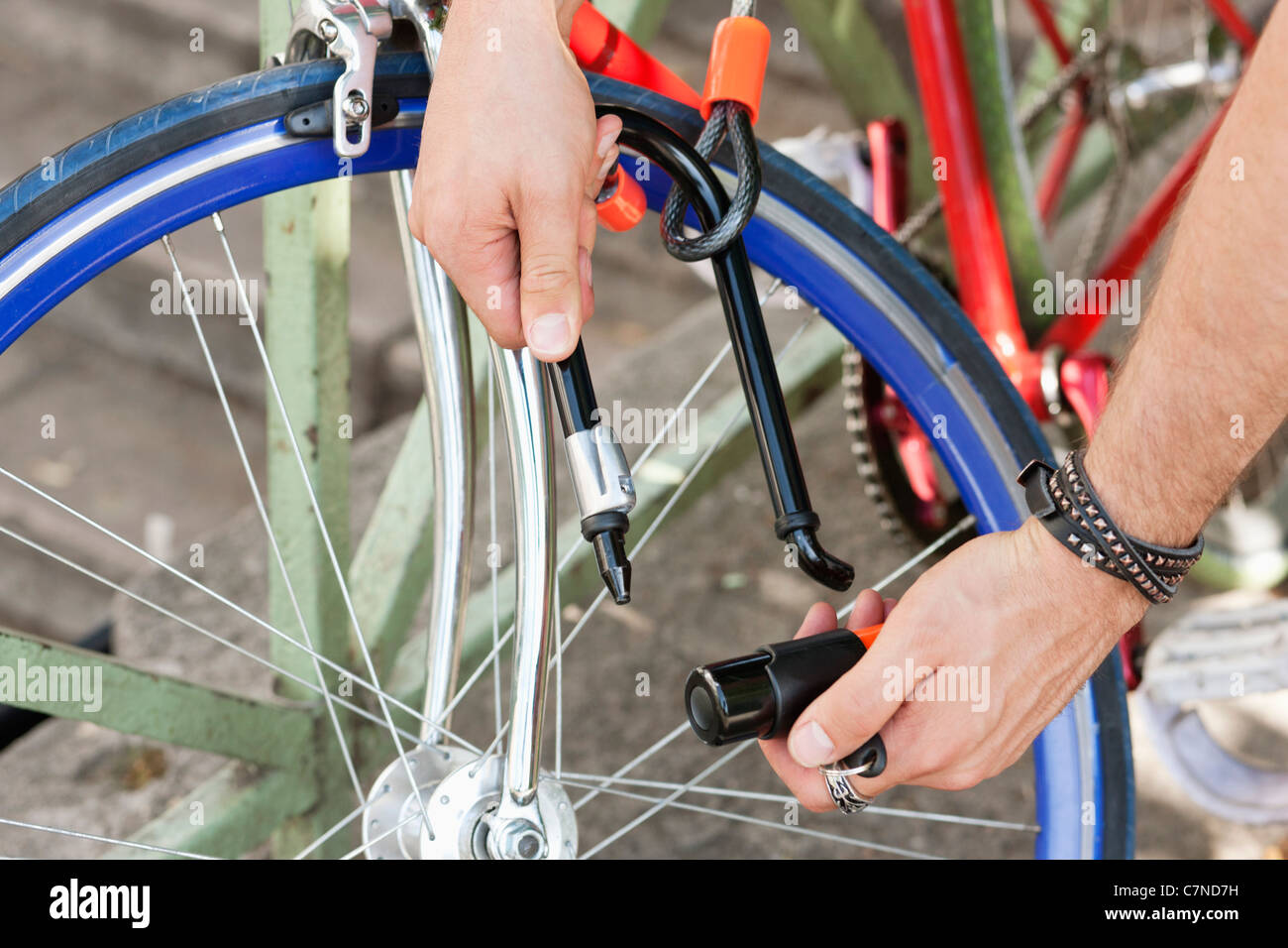 Close-up of a man's hands locking his bicycle, Paris, Ile-de-France, France - Stock Image
