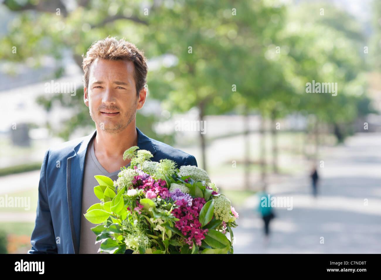 Man with a bouquet of flowers, Paris, Ile-de-France, France - Stock Image