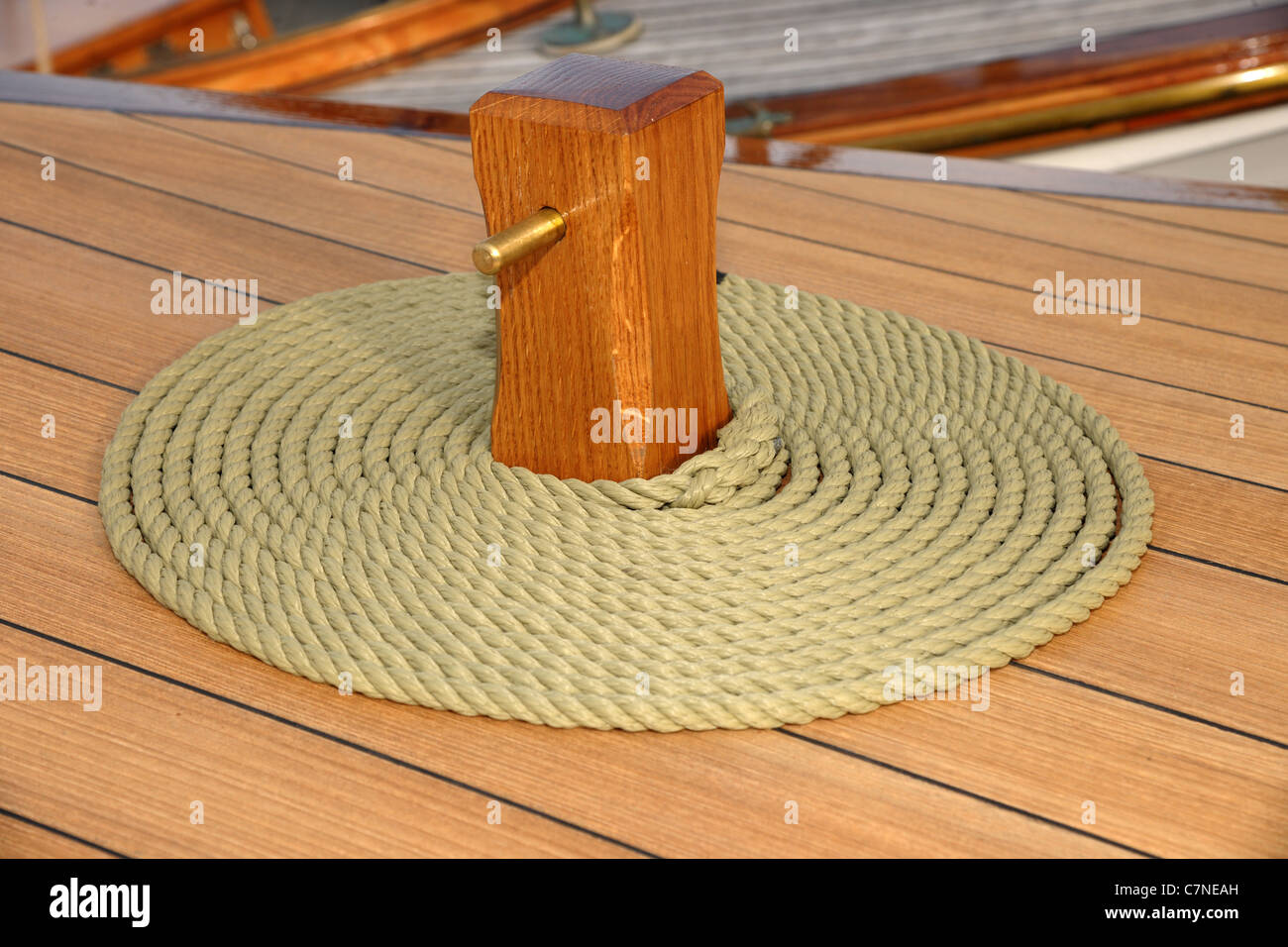 Coiled rope on teak deck. Decorative coiling is called 'cheesing' or 'flemish coil' and was used - Stock Image