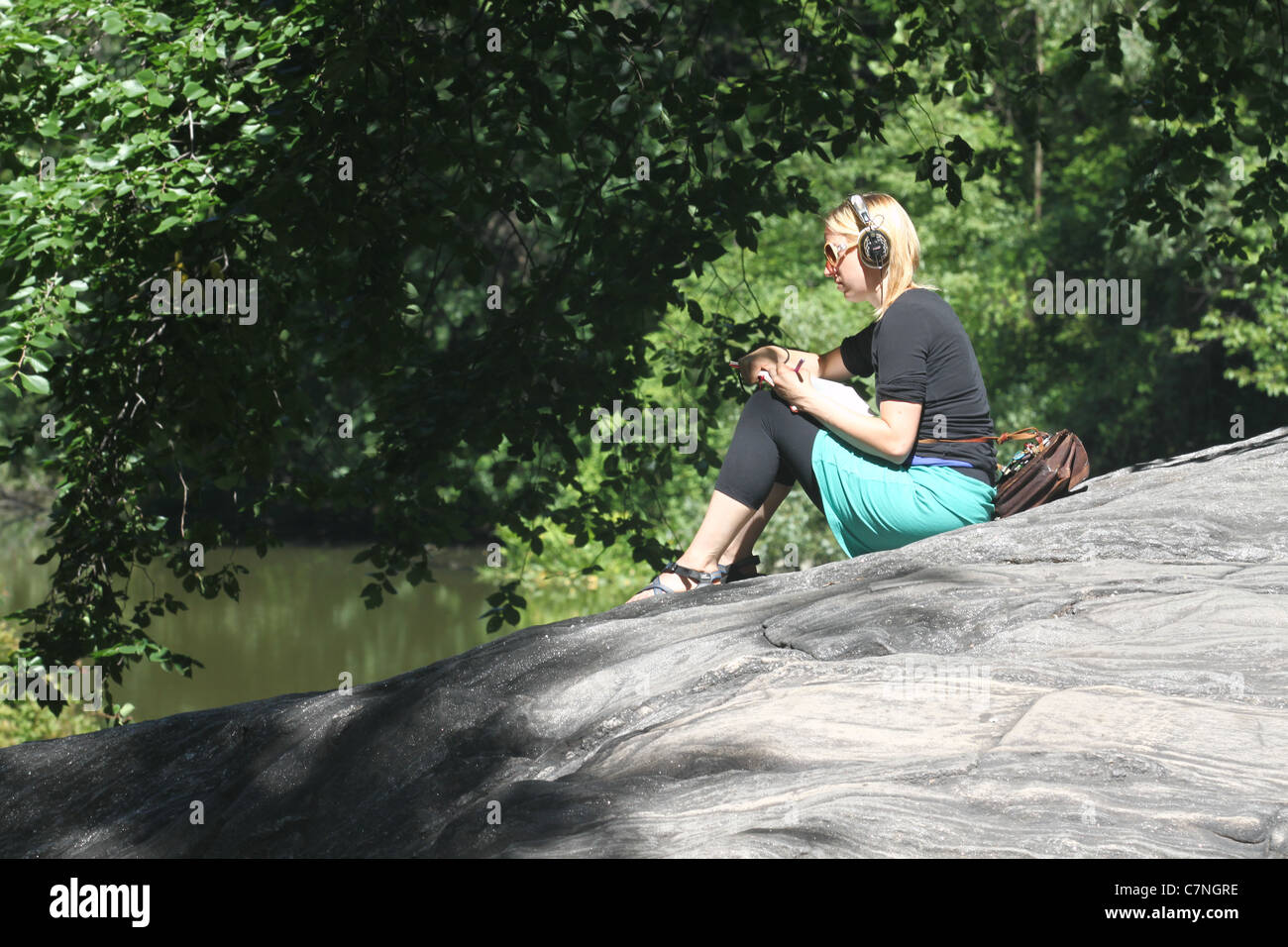 Blond girl listening to music in the park Stock Photo
