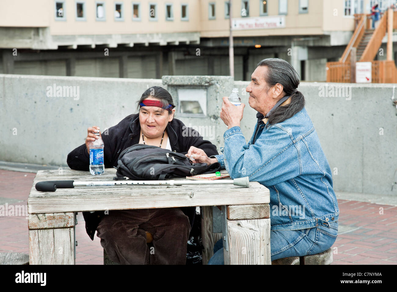 stoic genial senior native American Indian couple take a break with bottled water at rough wooden table in Seattle - Stock Image