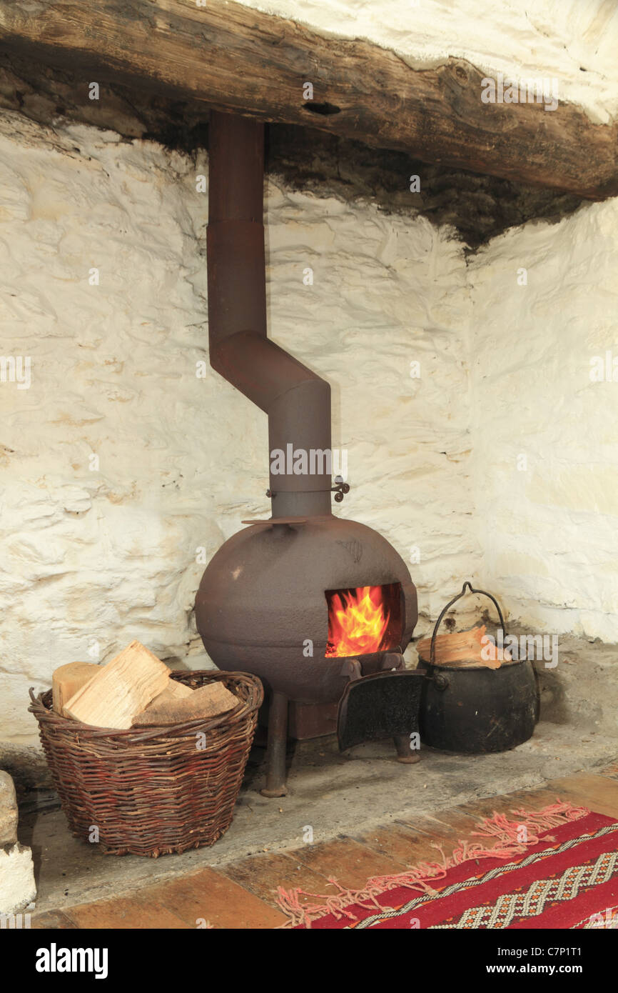 A pot bellied stove in a traditional Irish fireplace, County Kerry, Rep. of Ireland - Stock Image
