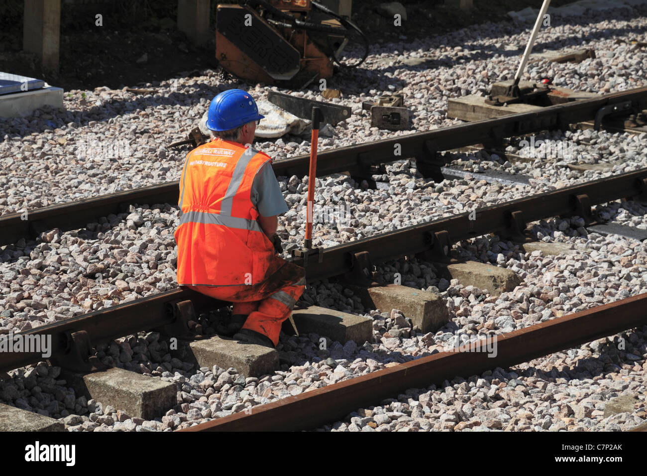 A railway engineer sighting the tracks at the Bluebell Railway, Sussex, England. - Stock Image
