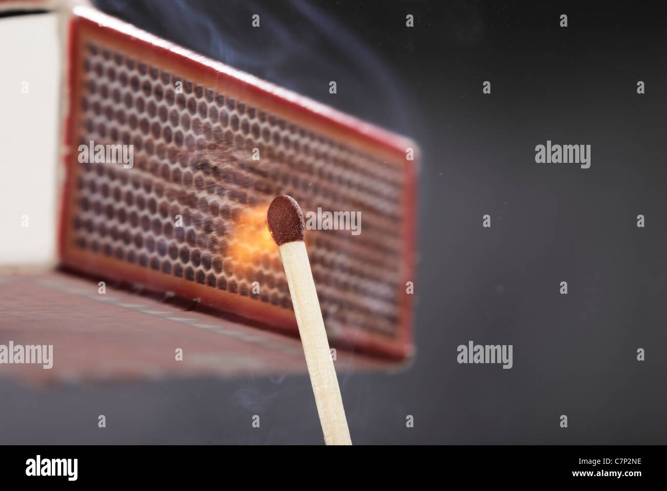 A Match ignited by rubbing the match head against a match box. - Stock Image