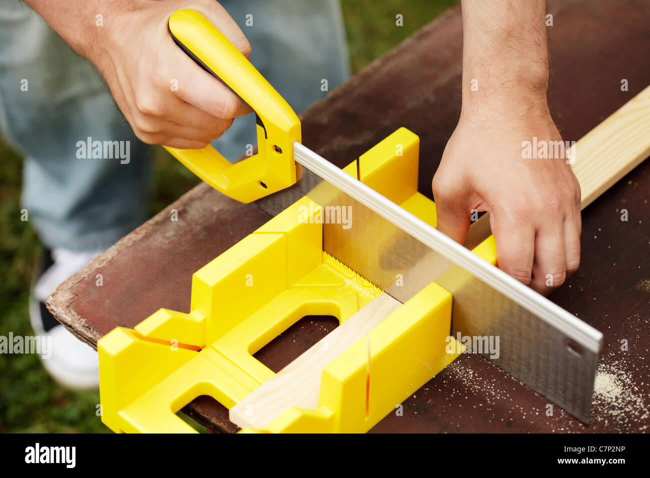 Man cutting a slat of wood using a saw and miter box outdoors. Stock Photo