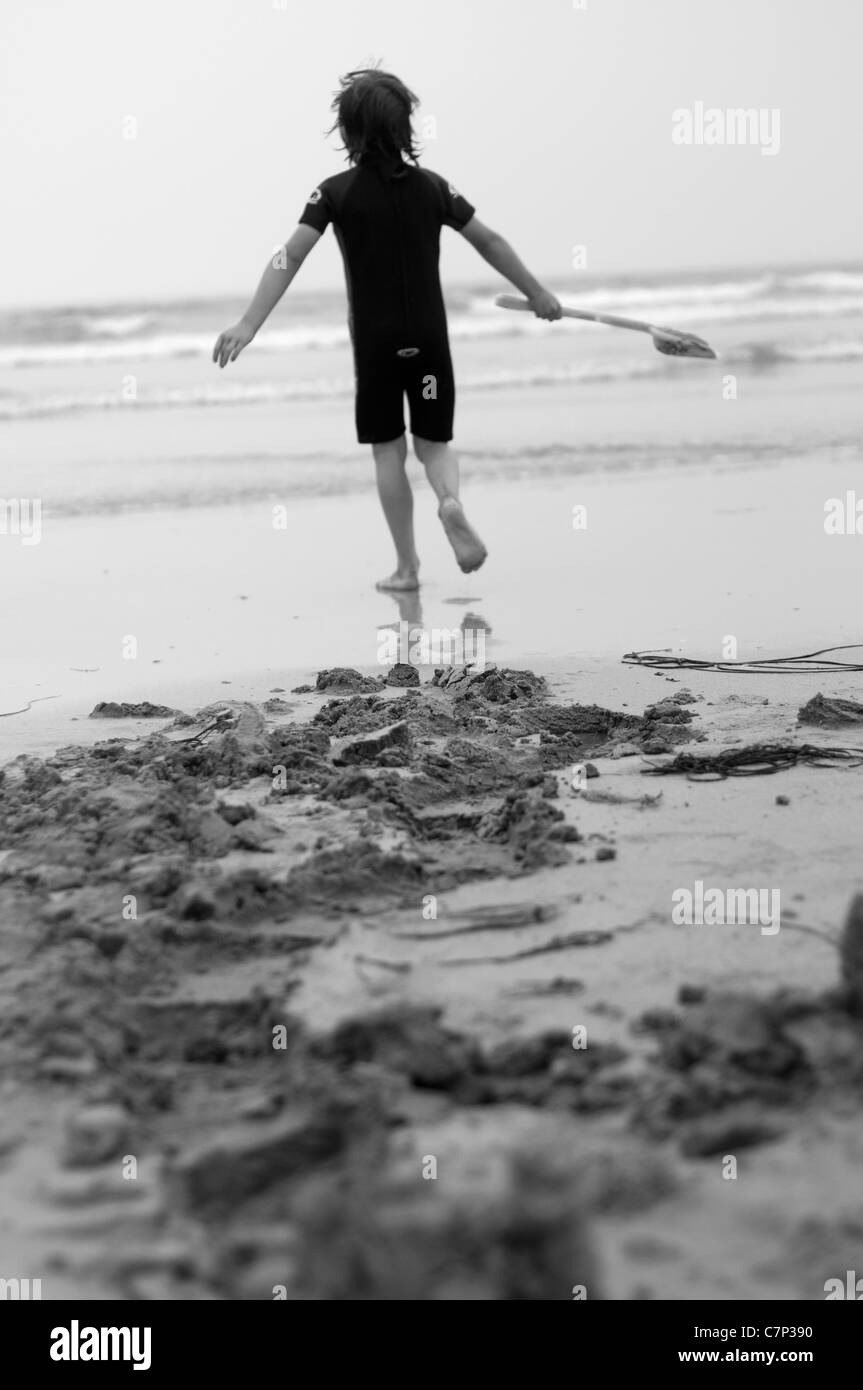 Boy running into the sea with his spade having dug up some sand. British seaside holiday. Black and white photograph - Stock Image