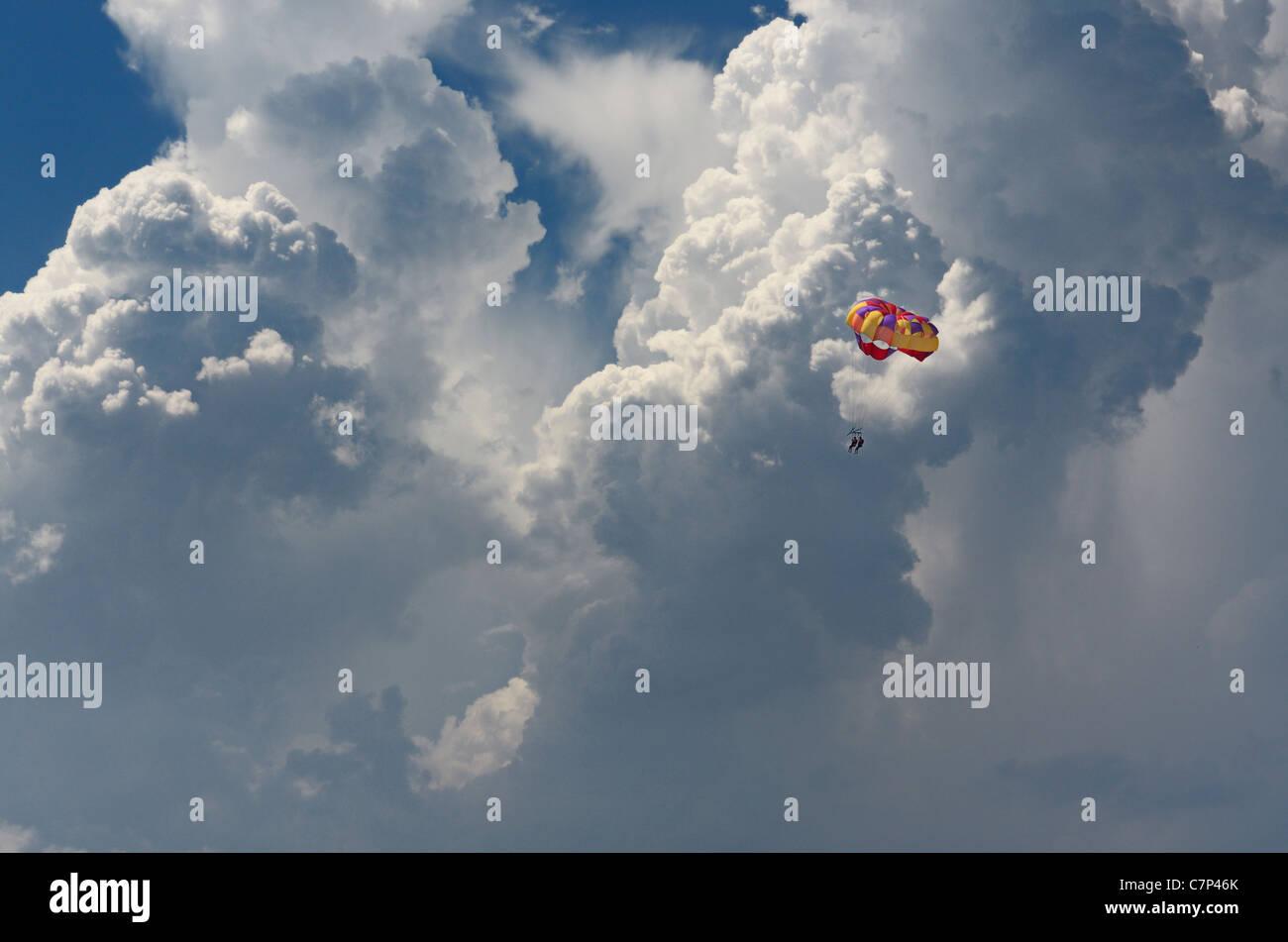 Pair of tourists parasailing against cumulonimbus clouds in Mexico - Stock Image