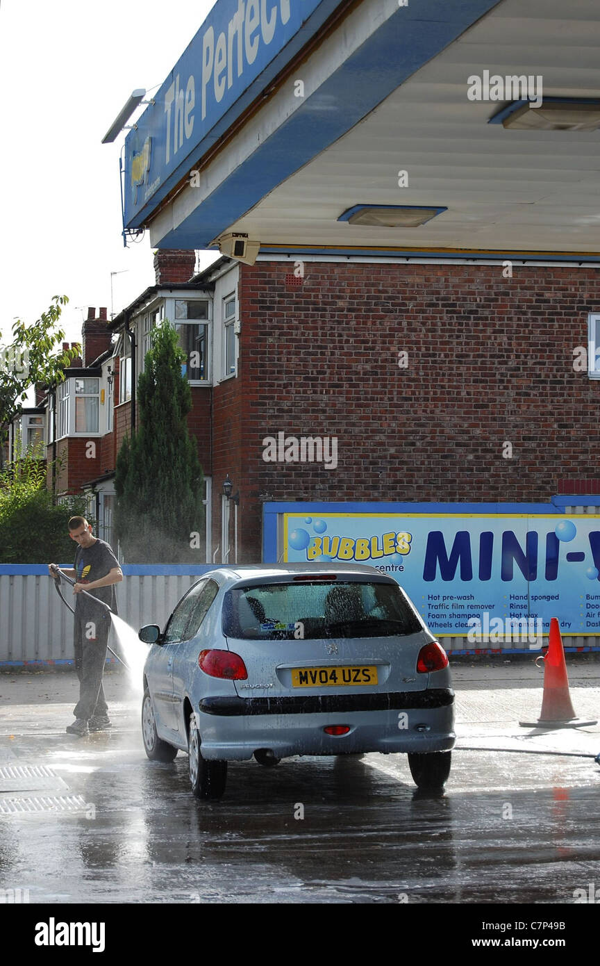 Car being sprayed at hand wash car facility before driving off - Stock Image