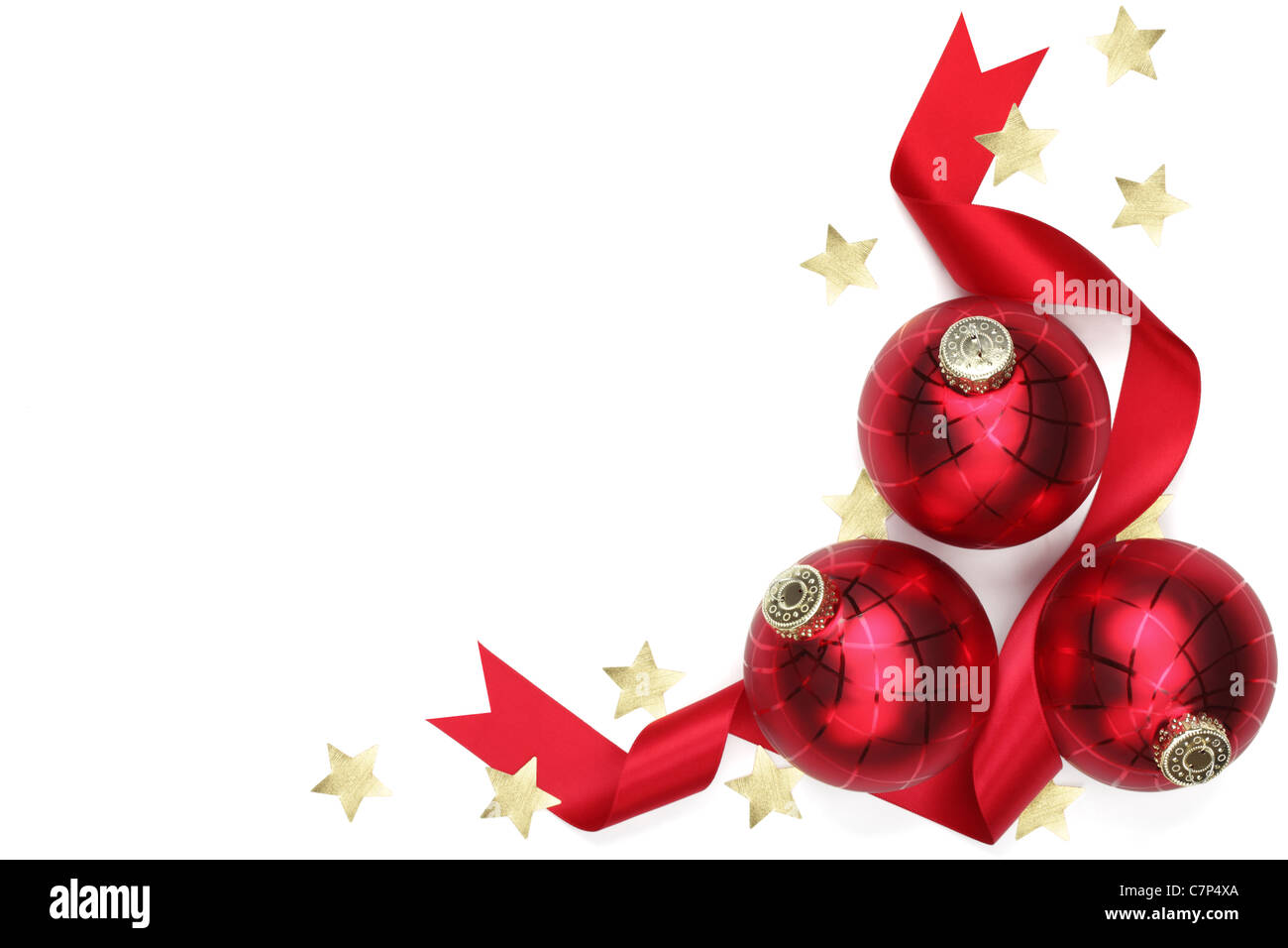 Three Christmas balls with ribbon and confetti stars on white background. - Stock Image