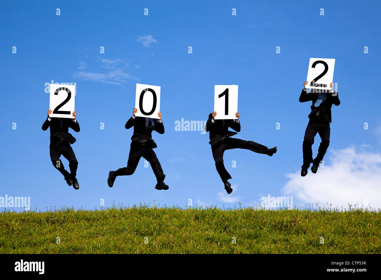 businessman holding 2012 billboard and jumping on the green field - Stock Image
