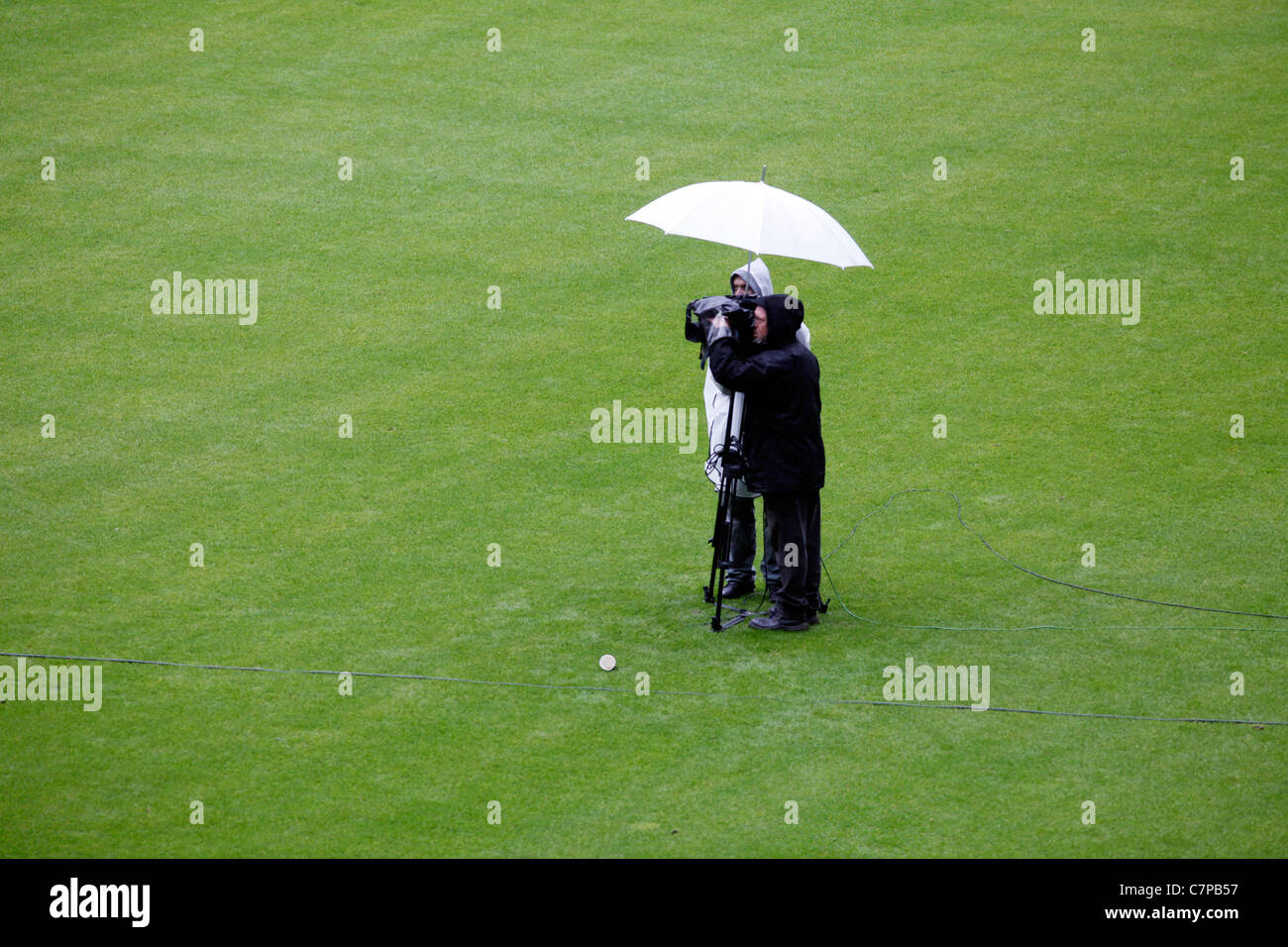 Television camera team, during a live coverage of an event, standing in heavy rain under an umbrella. Germany. - Stock Image
