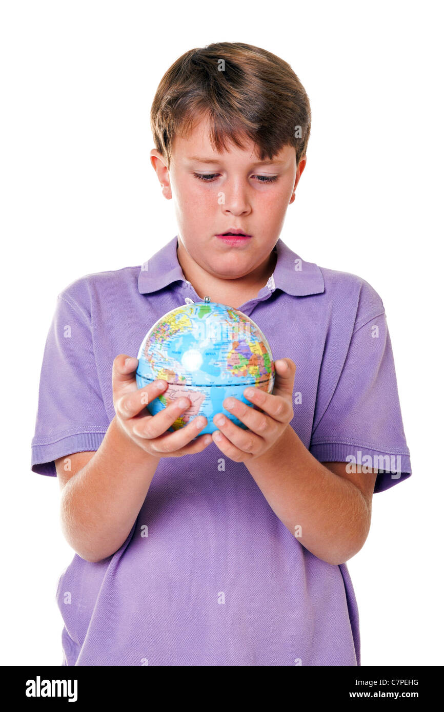 Photo of an 11 year old school boy holding a world globe, isolated on a white background. - Stock Image