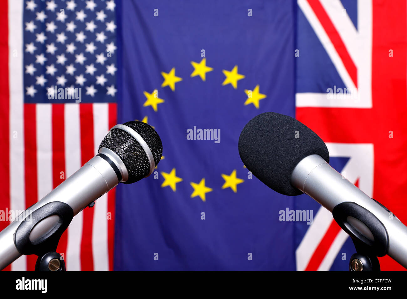 Two microphones on the stage of a press conference with the flags from America, European Union and the United Kingdom - Stock Image
