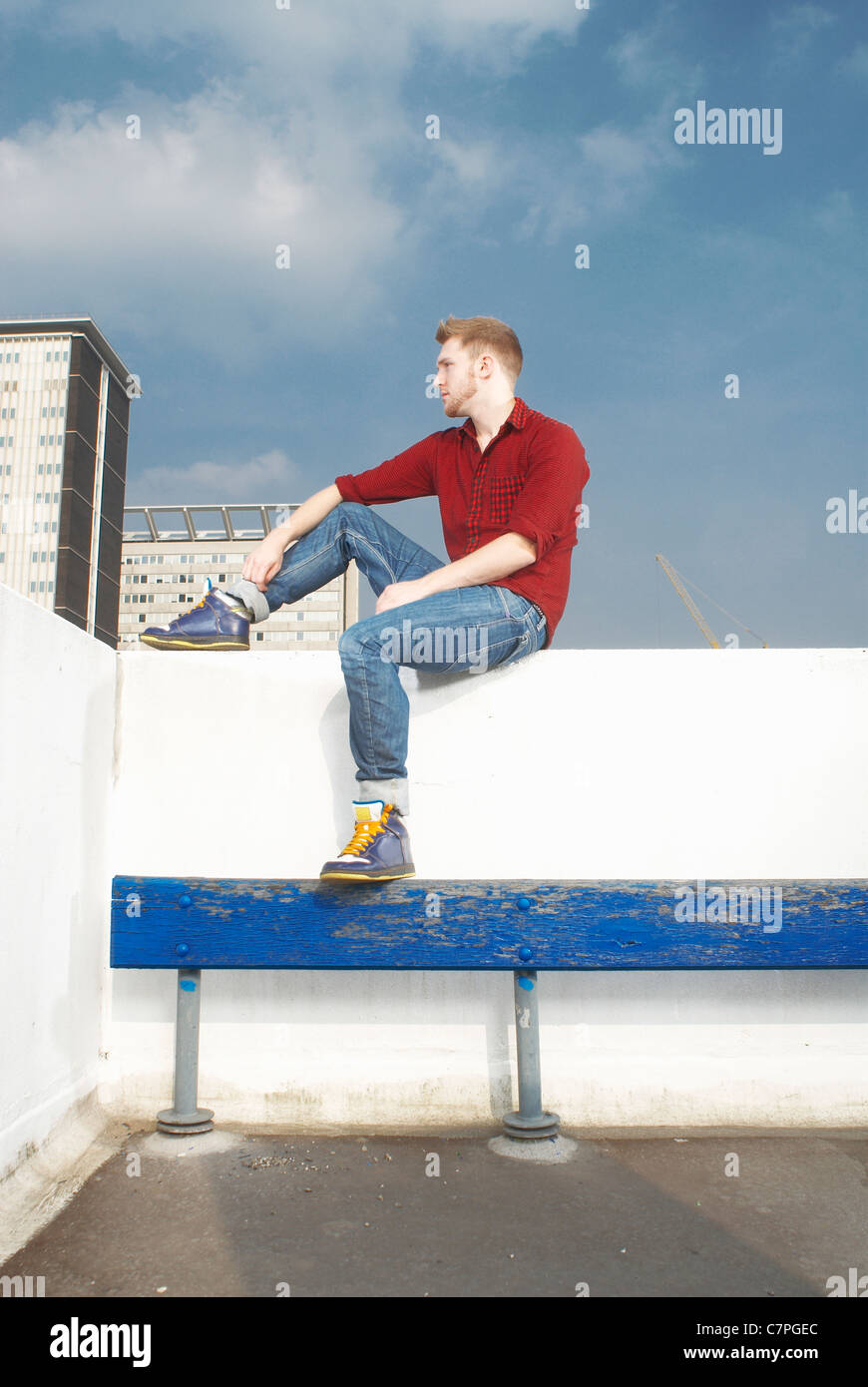 Man sitting on rooftop wall - Stock Image