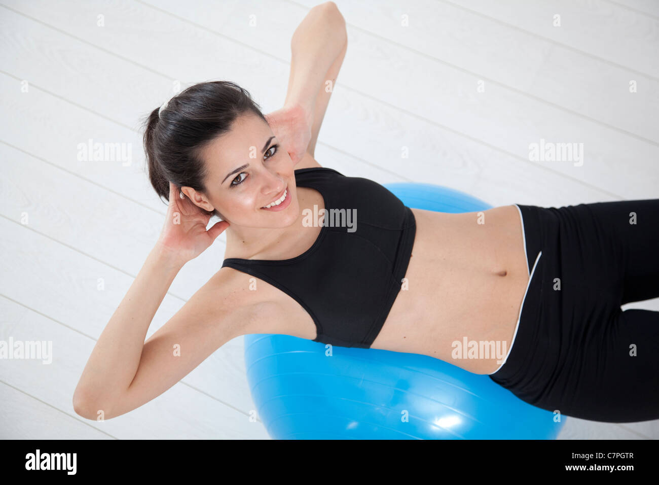 Woman doing sit-ups on exercise ball - Stock Image